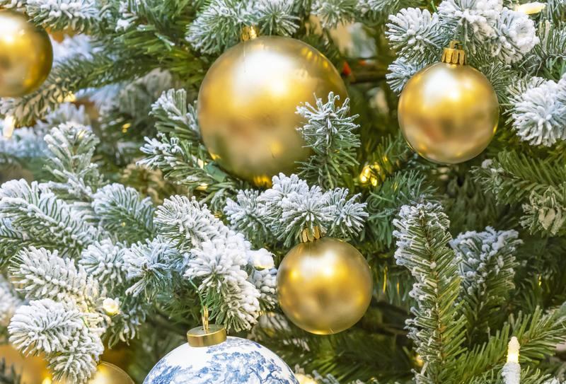 Золотые шарики и гирлянда на снежной рождественской елке стоковое изображение rf