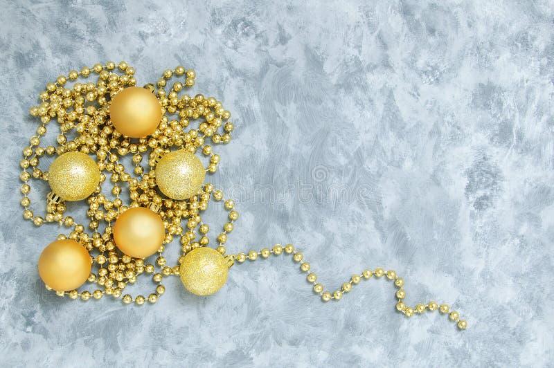 Золотые шарики строки и шариков рождества Против серой предпосылки стоковая фотография rf
