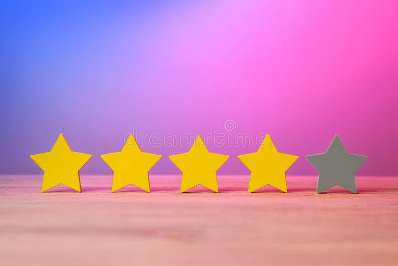 4 золотых желтых звезды из 5 На таблице звезды, оценка, обзор о фильме Красные фиолетовое и голубой стоковые изображения rf
