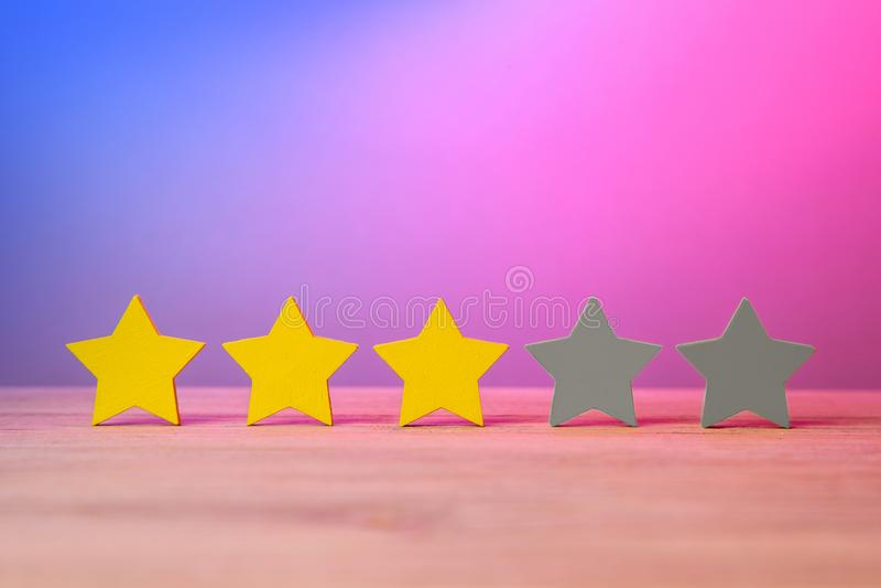 3 золотых желтых звезды из 5 На таблице звезды, оценка, обзор о фильме Красные фиолетовое и голубой стоковая фотография rf