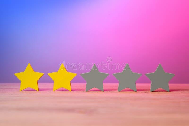 2 золотых желтых звезды из 5 На таблице звезды, оценка, обзор о фильме Красные фиолетовое и голубой стоковое фото