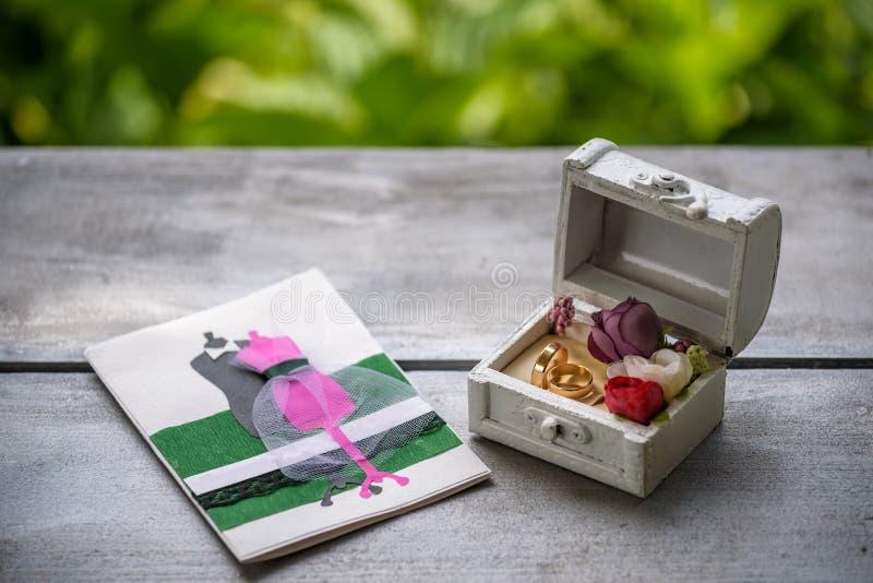 2 золотых обручального кольца в деревянной коробке и ветви белой акации с цветками и листьями на деревянной поверхности Карточка  стоковые изображения rf
