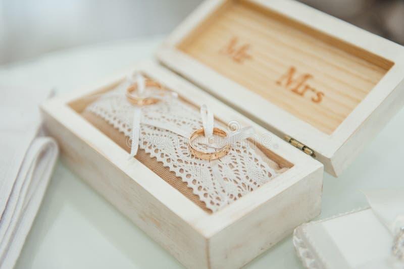 2 золотых обручального кольца в деревянной коробке на мягкой подушке Подготовка для церемонии стоковые фотографии rf