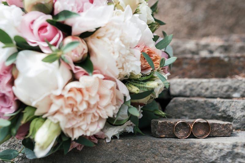 2 золотых обручального кольца на камне около красивого букета свадьбы белых и розовых пиона и роз в нерезкости outdoors стоковое фото