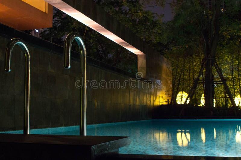 Зона бассейна на ноче с освещением нежности накаляя внешним в дорогом доме в тропической Юго-Восточной Азии с плоской водой и ro стоковое изображение rf
