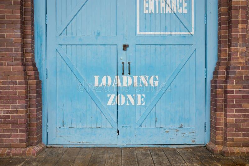 Зона загрузки покрашенная на голубой деревянной двери стоковое фото