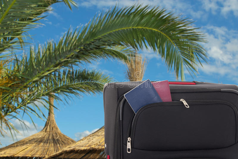Зонтики и чемодан с пасспортами на пляже стоковое изображение