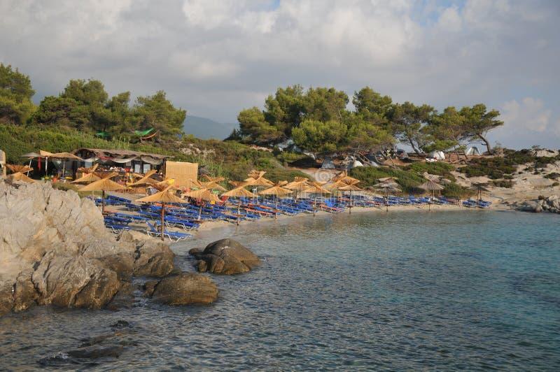 зонтики палубы стулов пляжа песочные стоковое изображение rf