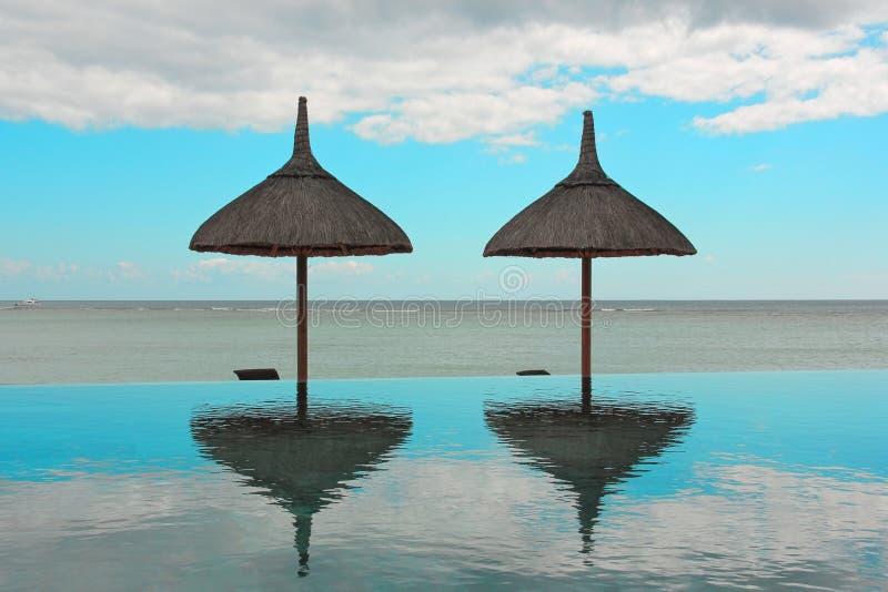 Зонтики пляжа и бассейн безграничности на тропическом курорте обозревая спокойный океан на летний день стоковая фотография rf