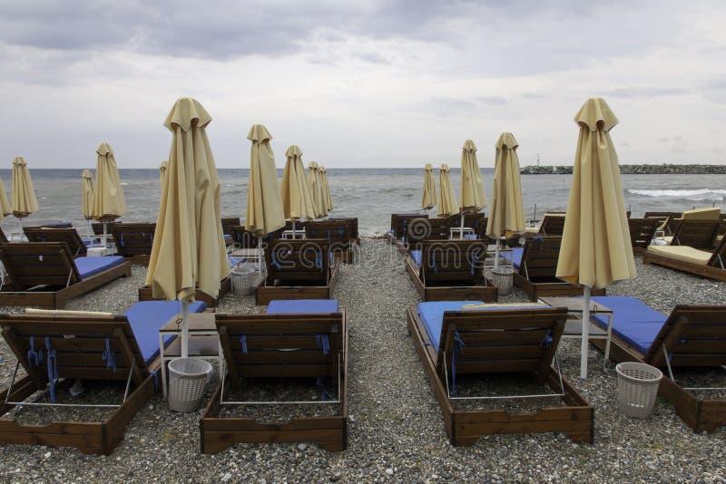 Зонтики пляжа и пустые кресла для отдыха на пасмурный день Platamonas стоковое фото