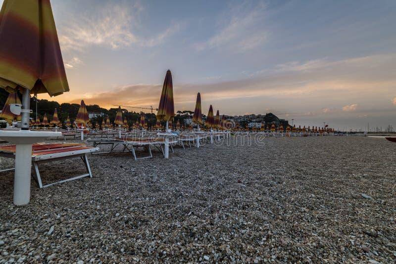 Зонтики пляжа около городка Numana на заходе солнца, Conero NP, мамах стоковые фотографии rf