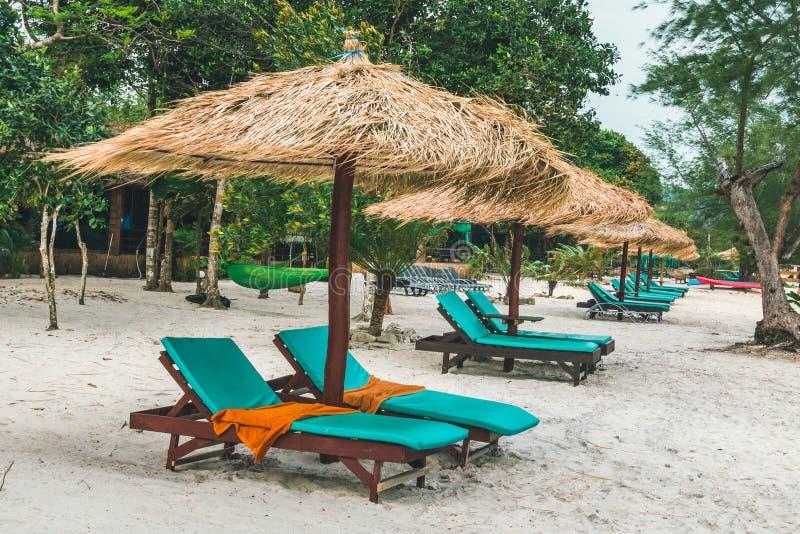 Зонтики сделанные из соломы и шезлонга сделали из древесины на чудесном тропическом пляже, красивом пляже, лазурном море и белом  стоковое фото