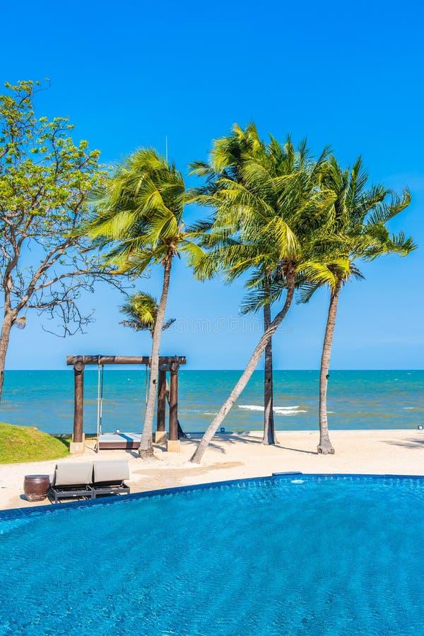 Зонтик и стул вокруг бассейна в пляже океана моря курорта гостиницы neary на каникулы стоковое фото