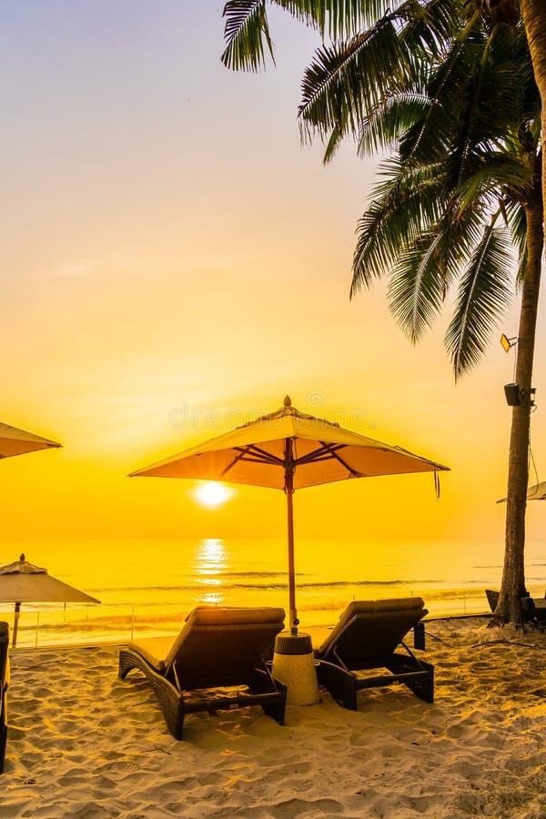 Зонтик и стул на красивом пляже и море на времени восхода солнца на перемещение и каникулы стоковое изображение
