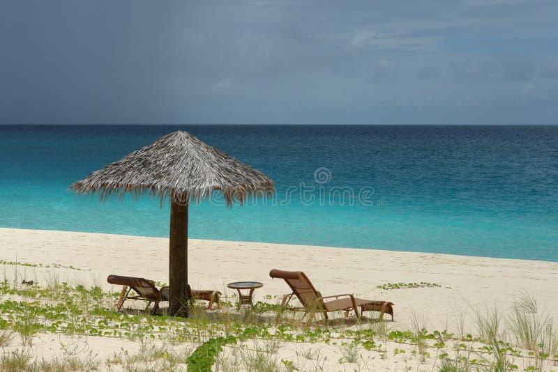 Зонтик и стулья пляжа с открытым морем и raincloud стоковое фото
