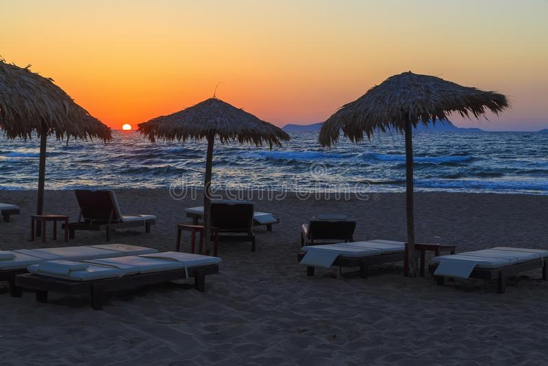 Зонтик пляжа на заходе солнца, взгляде стульев и зонтиках на пляже Заход солнца на море красивое небо на пляже Деревянный пляж стоковое изображение