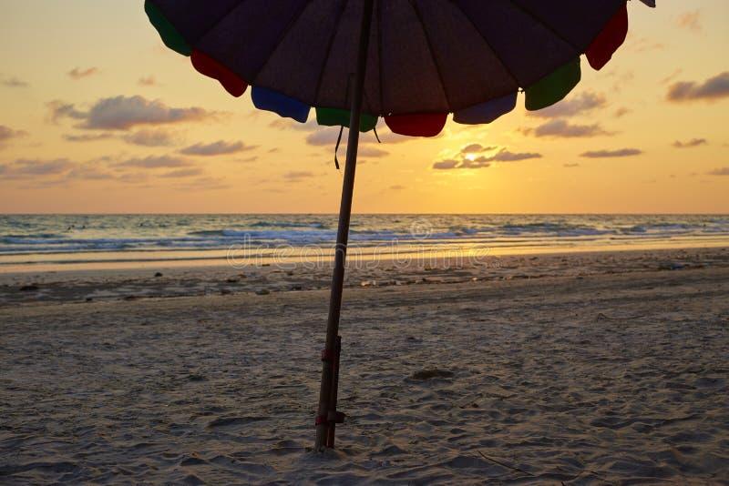 Зонтик пляжа силуэта с заходом солнца на море стоковая фотография