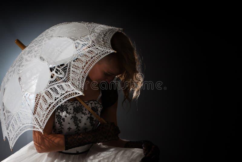Зонтик темной романтичной женщины сказки сидя стоковая фотография rf