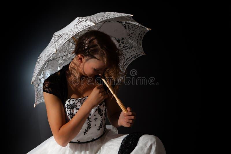 Зонтик темной романтичной женщины сказки сидя стоковая фотография