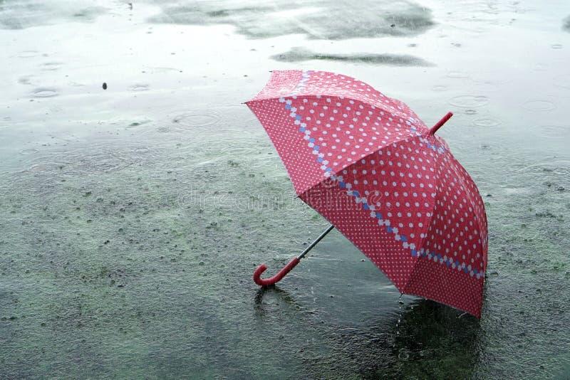Зонтка в дождливый день - капельки, падающие на зонтик, которые лежат на земле и копируют пространство, чувствуя себя одиноко и г стоковые фотографии rf
