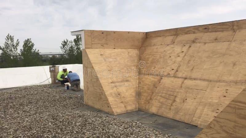 Зоны Roofers ремонтируя коммерчески плоской крыши, деревянного основания панели построенного вверх по стене стоковые изображения