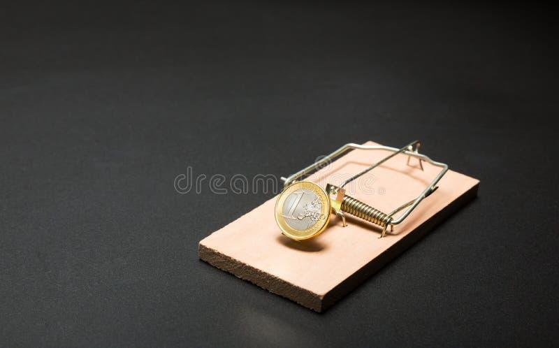 Золотая монетка в ловушке мыши стоковые фото