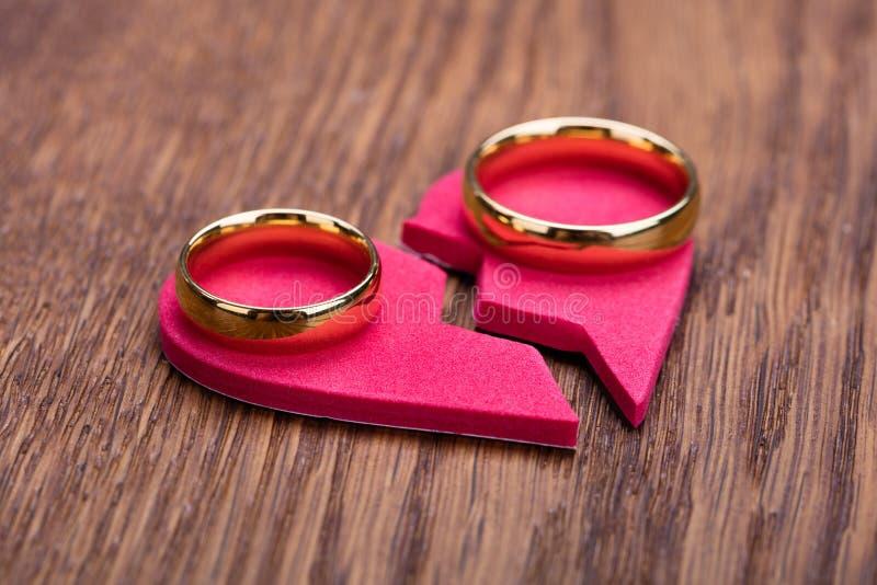 Золотое кольцо на красном разбитом сердце стоковые фото
