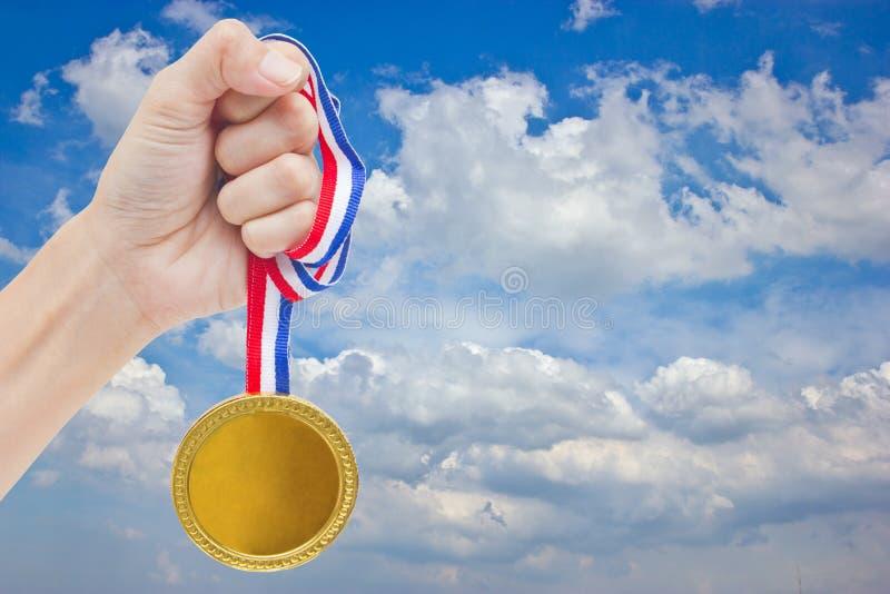 Золотое медаль в руке женщины. стоковая фотография