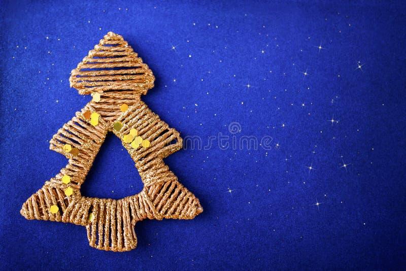 Золотое украшение ели рождества на предпосылке сини яркого блеска стоковая фотография rf