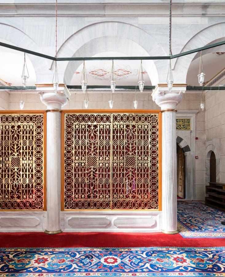 Золотой богато украшенный пефорированный раздел обрамленный в белом мраморном своде и богато украшенном ковре стоковые изображения rf