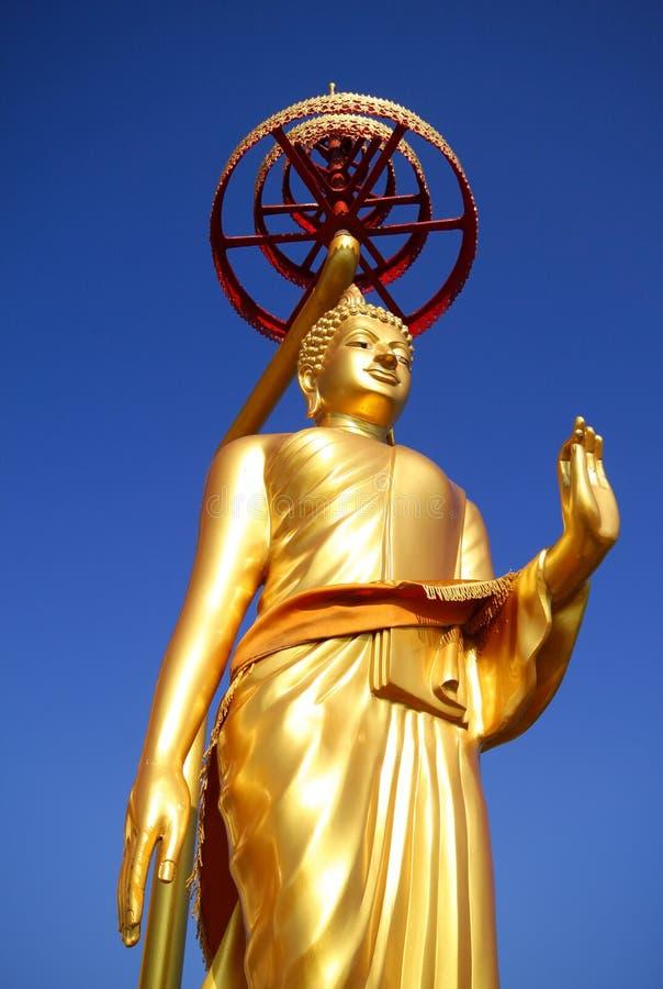 Золотой Будда в предпосылке голубого неба Таиланда стоковое изображение