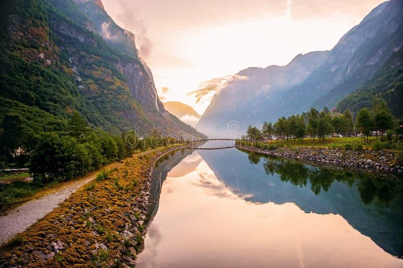 Золотой восход солнца в горах, Gudvangen Норвегия с отражением в воде фьорда Горизонтальная рамка стоковая фотография