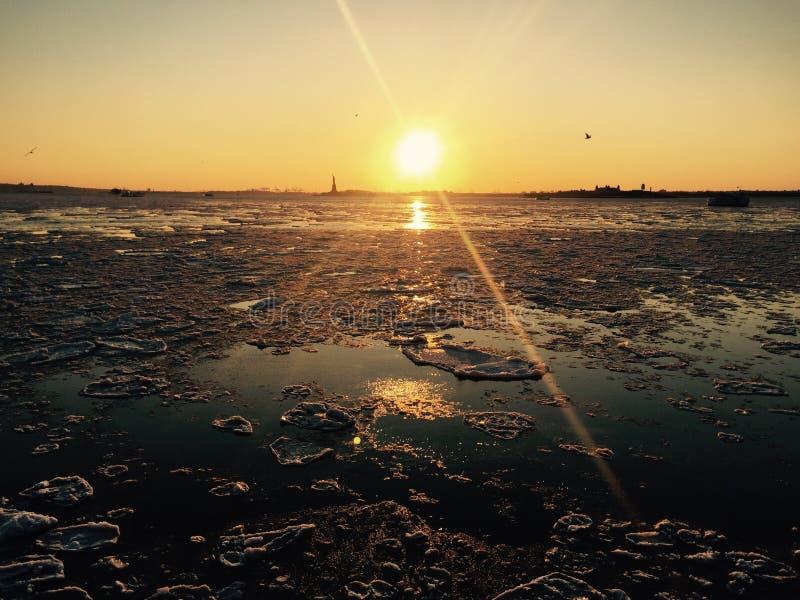 Золотой заход солнца над замороженным рекой стоковое фото rf