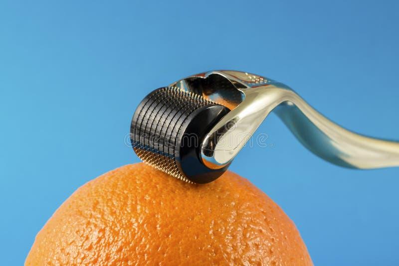Золотой ролик derma для медицинской микро- needling терапии с апельсином стоковые изображения rf