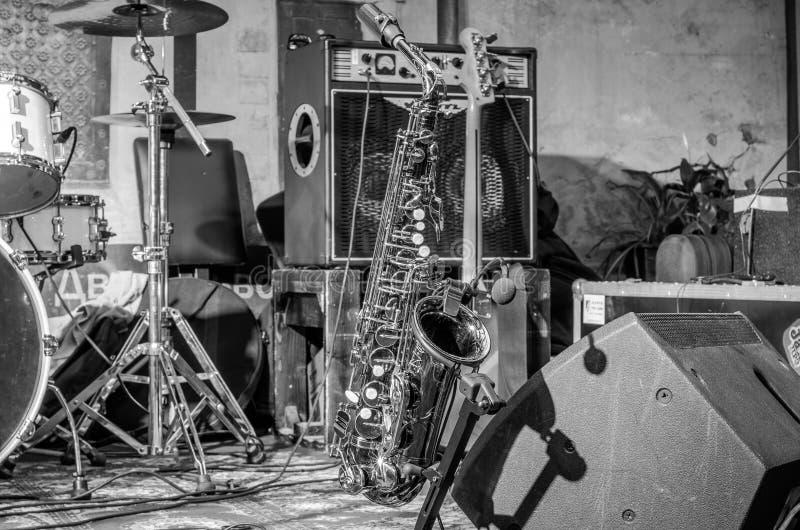 Золотой саксофон стоит на этапе рядом с другими музыкальными инструментами стоковые изображения