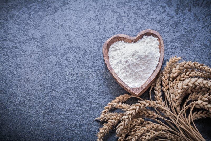 Золотой шар ушей пшеницы и рож деревянный с мукой стоковое фото
