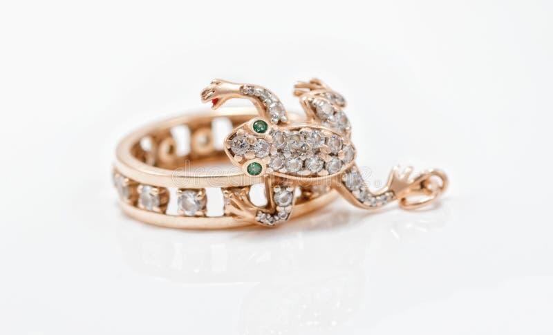 Золотой шкентель в форме лягушки вползает в кольце золота стоковые фотографии rf