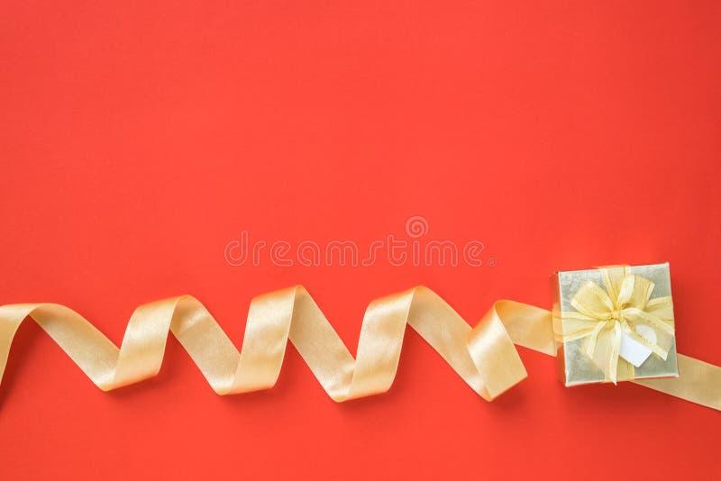Download Золотые лента и подарочная коробка на красной предпосылке Стоковое Фото - изображение насчитывающей золотисто, взгляд: 81811866