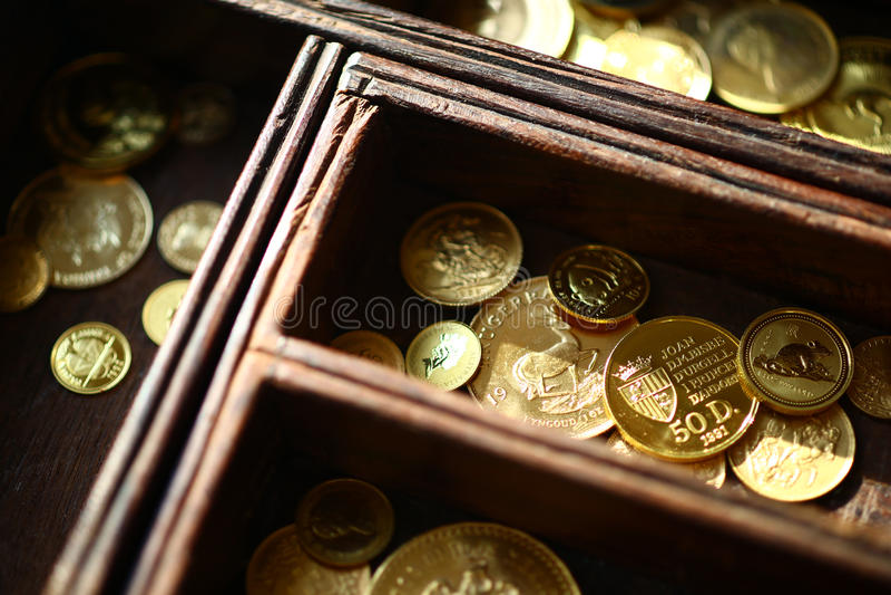 Золотые монетки в деревянном ларце стоковое фото