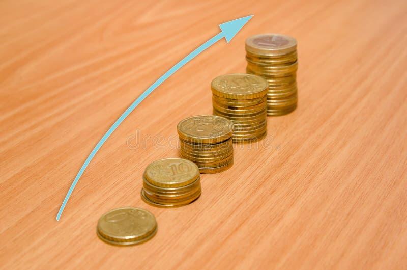 Золотые монетки евро с стрелкой стоковое изображение