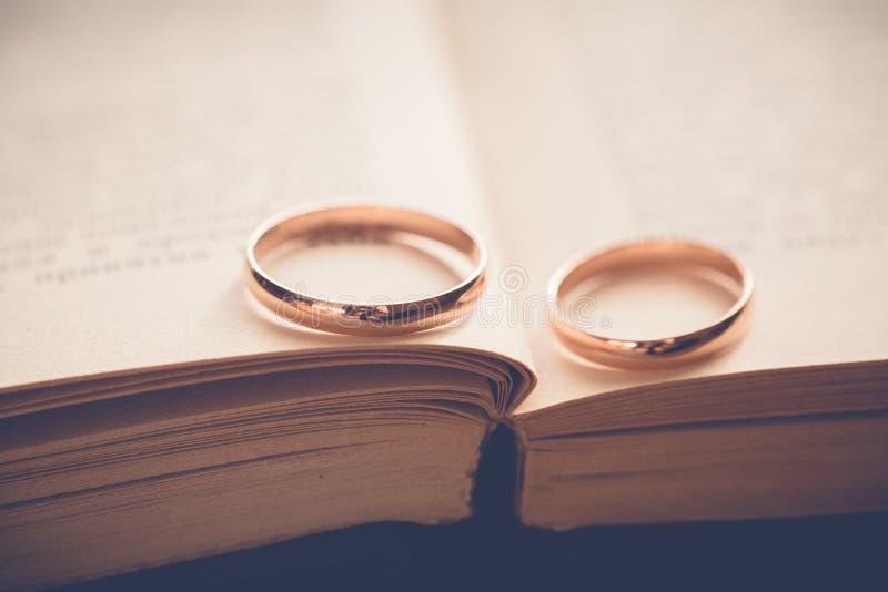 Золотые обручальные кольца на книге стоковое фото rf