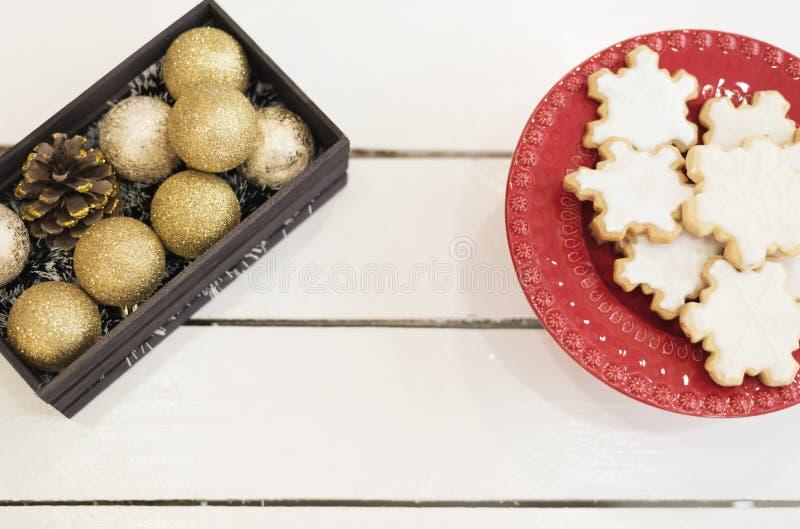 Золотые шарики в деревянной клети, печенья рождества рождества сформировали в снежинках в красном подносе на белой деревенской де стоковое изображение rf
