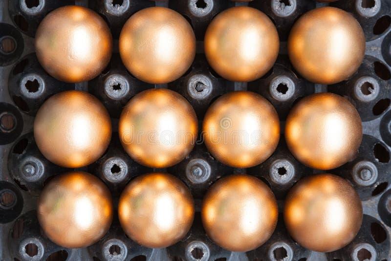 Золотые яичка на черном пакете стоковые изображения rf