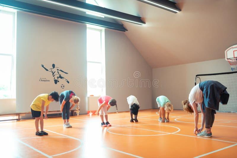 Зрачки гнуть над на уроком спорт с их тренером стоковые изображения rf