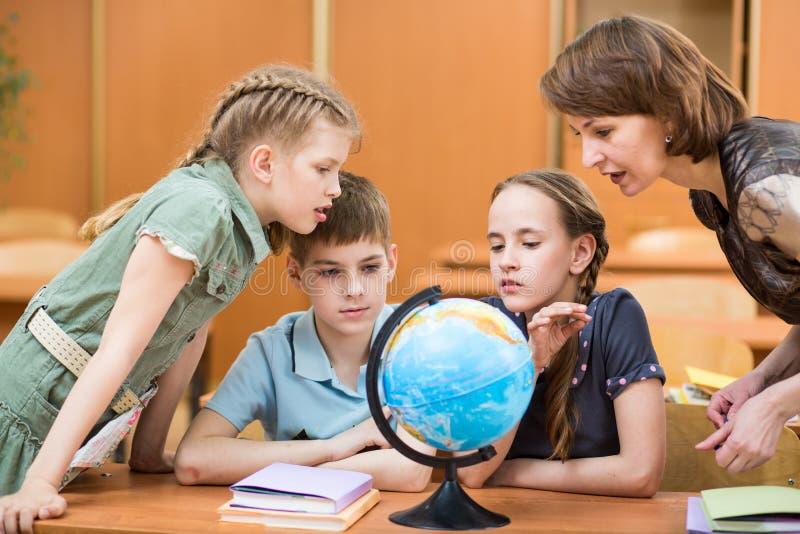 Зрачки изучая глобус вместе с учителем стоковые фото