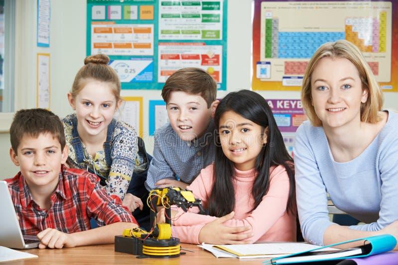 Зрачки и учитель в уроке науки изучая робототехнику стоковые изображения rf
