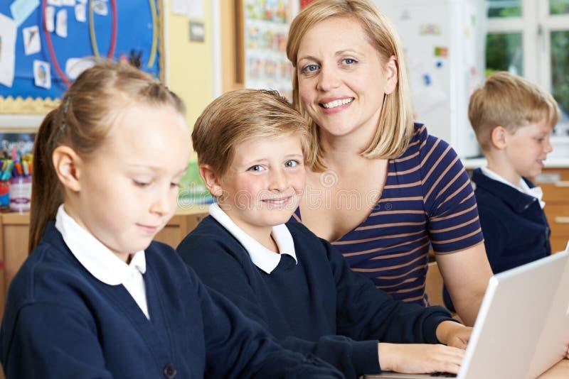 Зрачки начальной школы порции учителя в классе компьютера стоковые фото