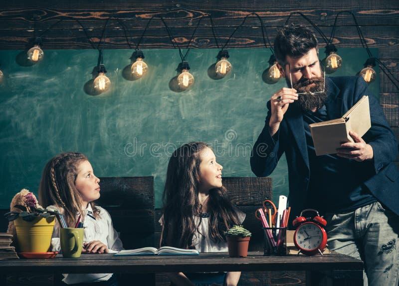 Зрачки учителя и девушек в классе, доске на предпосылке Учитель любознательных жизнерадостных детей слушая с стоковые изображения