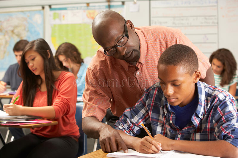 Зрачок порции учителя мужской изучая на столе в классе стоковые фотографии rf