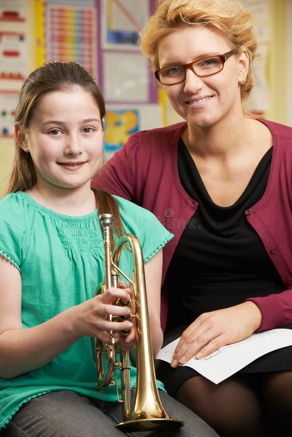 Зрачок порции учителя для того чтобы сыграть трубу в уроке музыки стоковые изображения
